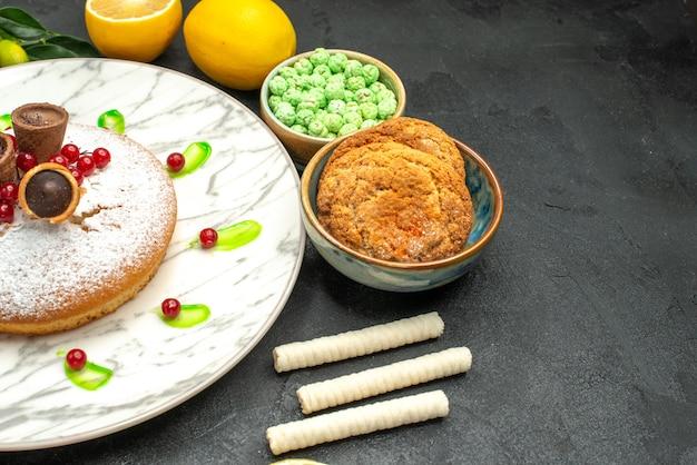 Zijaanzicht close-up een cake een cake met wafels citroenen groene snoepjes cookies