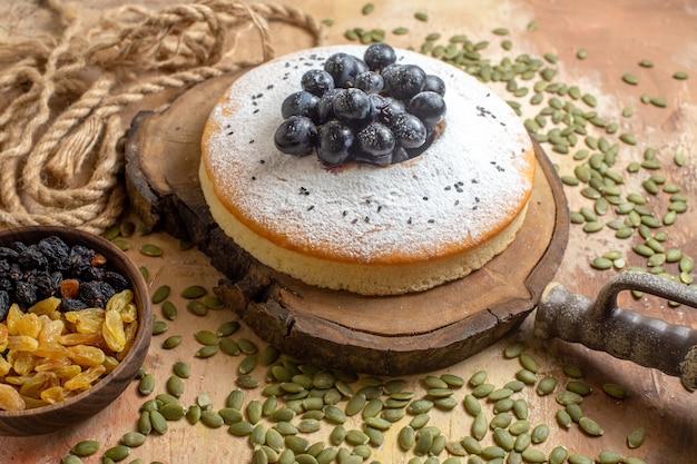 Zijaanzicht close-up een cake rozijnen in de kom een cake met zwarte druiven pompoenpitten touw