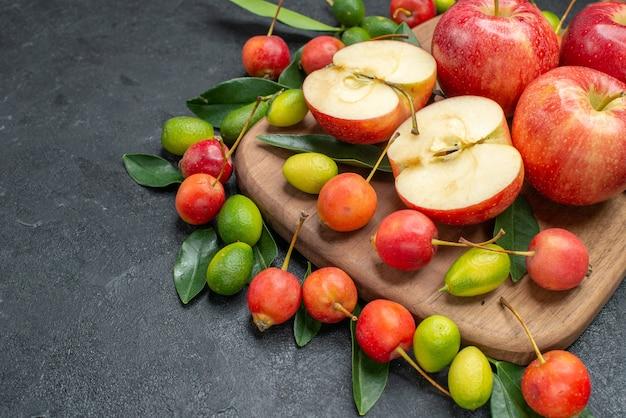 Zijaanzicht close-up fruit rode appels kersen citrusvruchten op het bord