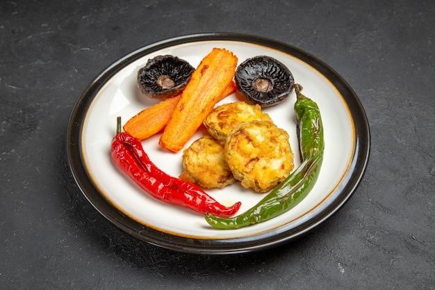 Zijaanzicht close-up geroosterde groenten de smakelijk geroosterde wortelen hete pepers champignons