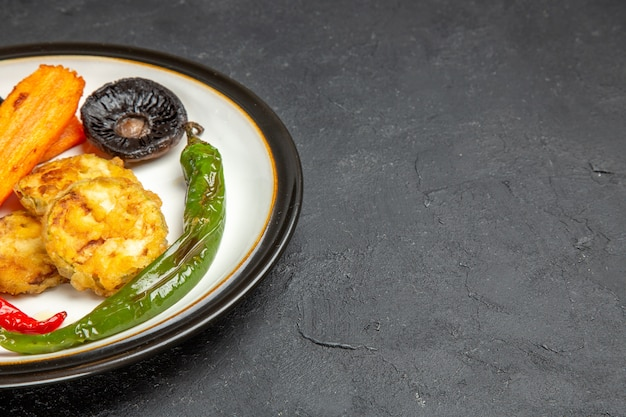 Zijaanzicht close-up geroosterde groenten plaat van de smakelijke geroosterde hete pepers champignons