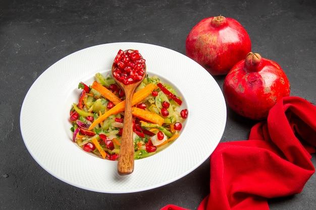 Zijaanzicht close-up granaatappel twee granaatappels groente salade lepel met zaden van granaatappels
