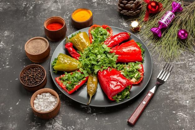Zijaanzicht close-up plaat van paprika specerijen vork de smakelijke paprika kegel