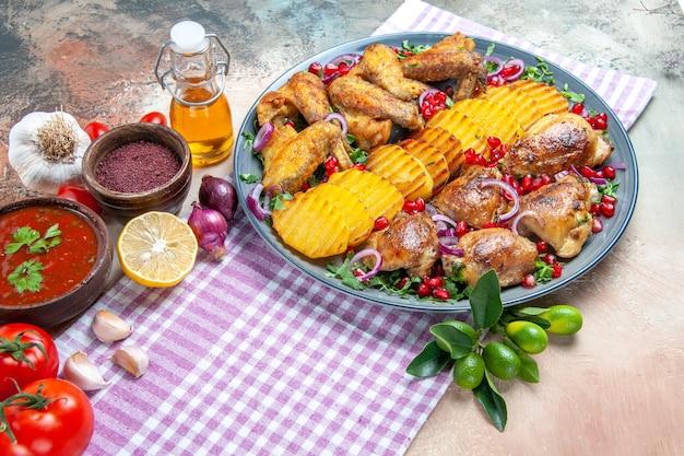Zijaanzicht close-up schotel kip met aardappelsaus tomaten kruiden olie knoflook op het tafellaken