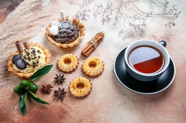Zijaanzicht close-up snoep een kopje thee cupcakes koekjes citrusvruchten steranijs