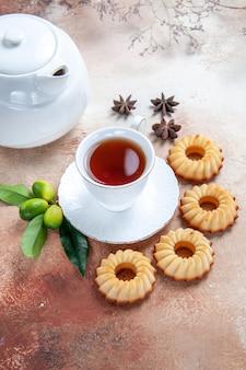 Zijaanzicht close-up snoep een kopje thee koekjes theepot steranijs