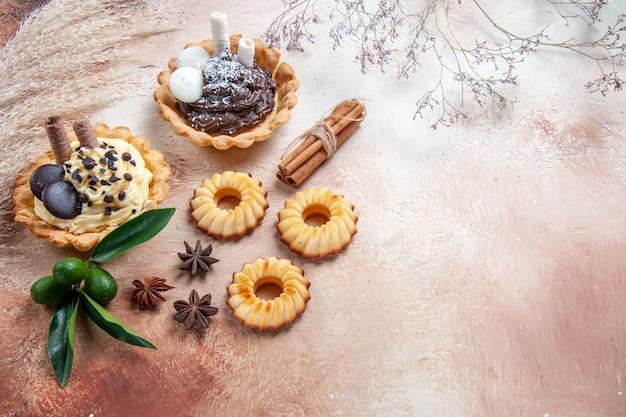 Zijaanzicht close-up snoep koekjes cupcakes citrusvruchten kaneelstokjes