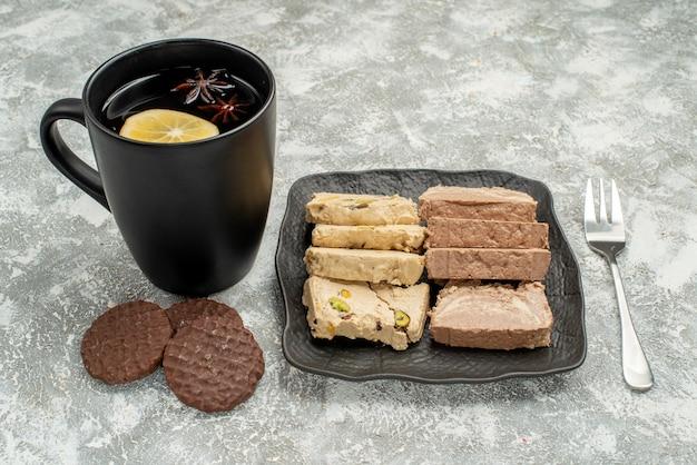 Zijaanzicht close-up snoep zonnebloempitten halva op de plaat vork een kopje thee koekjes
