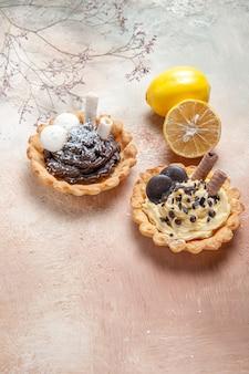 Zijaanzicht close-up snoepjes citroen twee cupcakes op tafel