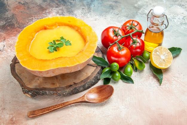 Zijaanzicht close-up soeplepel tomaten citrusvruchten olie pompoensoep op het bord
