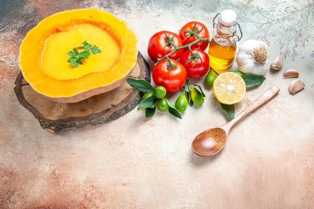 Zijaanzicht close-up soeplepel tomaten knoflook citrusvruchten olie pompoensoep op het bord