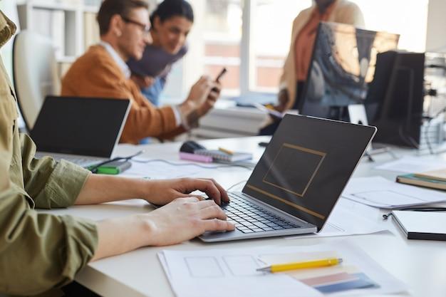 Zijaanzicht close-up van it-programmeur die code schrijft op laptopscherm terwijl u werkt in softwareproductiestudio met focus op mannelijke handen typen op toetsenbord, kopieer ruimte