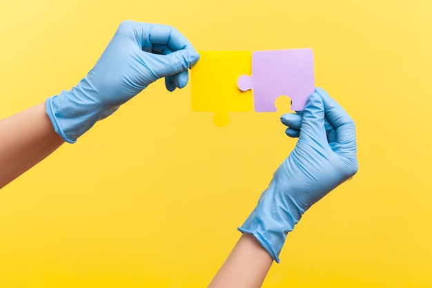 Zijaanzicht close-up van menselijke hand in blauwe chirurgische handschoenen met gele en paarse puzzel pieses.