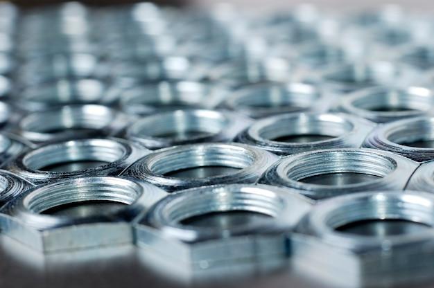 Zijaanzicht close-up verchroomde metalen moeren in de vorm van honingraten liggen naast elkaar en vormen een gebied. het concept van bevestigingsmiddelen en constructie. reparatie- en onderdelenconcept