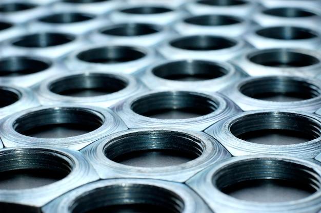 Zijaanzicht close-up verchroomde metalen moeren in de vorm van honingraten liggen naast elkaar en vormen een gebied.