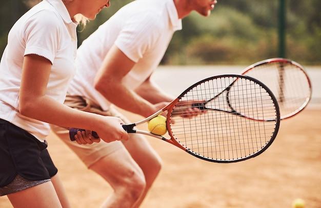Zijaanzicht. coach lesgeven vrouwelijke student tennisspel in de rechtbank buitenshuis.