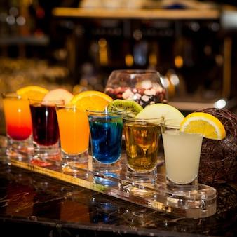 Zijaanzicht cocktail shots met schijfje citroen en kiwi schijfje en appel schijfje