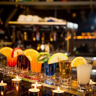 Zijaanzicht cocktail shots met schijfje citroen en kiwi segment en kaarsen op bar