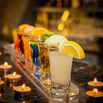Zijaanzicht cocktail shots met schijfje citroen en kiwi segment en kaarsen