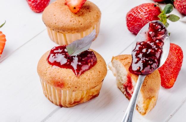 Zijaanzicht cupcakes met aardbeijam en basilicum op witte achtergrond