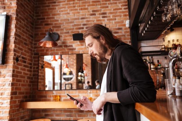 Zijaanzicht dat van de mens zich op bar met telefoon bevindt