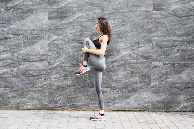 Zijaanzicht dat van geschikte jonge vrouw is ontsproten die cardio-intervaltraining doet tegen grijze muur.