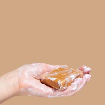 Zijaanzicht dat van hand schuimende zeep met exemplaarruimte houdt