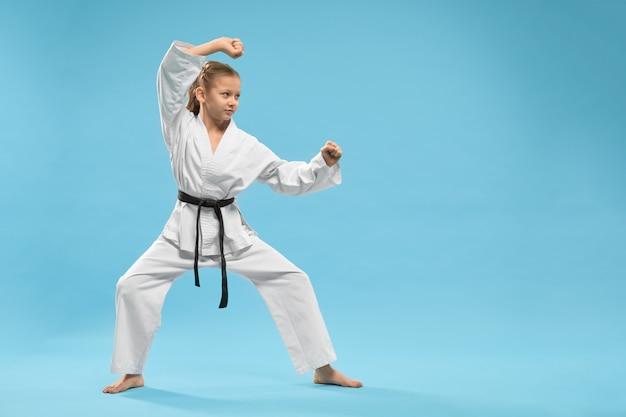Zijaanzicht dat van kind zich in karatestand bevindt in studio