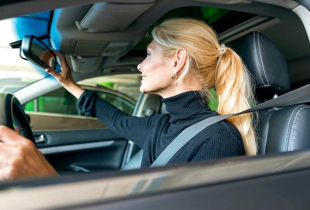 Zijaanzicht dat van oudere bedrijfsvrouw haar autospiegel aanpast