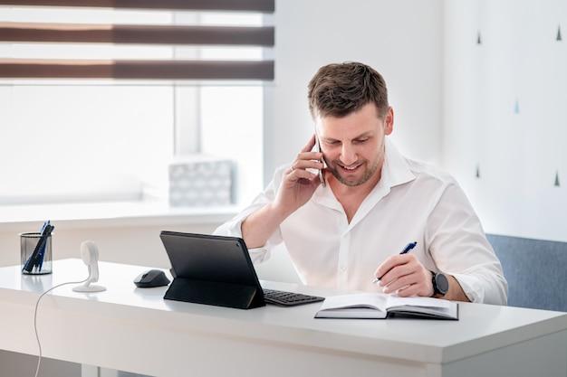 Zijaanzicht dat van peinzende jonge mensenzitting thuis is ontsproten en aan laptop werkt. kaukasisch mannetje dat van huisbureau werkt.