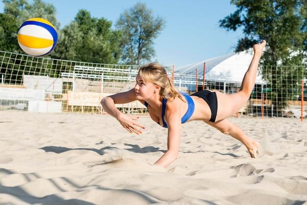 Zijaanzicht dat van vrouw bereikt om volleyball te raken alvorens het het zand raakt