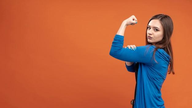 Zijaanzicht dat van vrouw haar biceps met exemplaarruimte toont