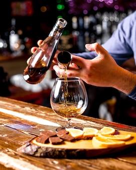 Zijaanzicht de barman stroomt uit een beker whisky met chocolade en stukjes sinaasappel