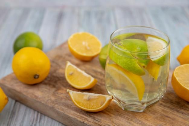Zijaanzicht detox water in een glas met partjes limoen en een halve sinaasappel en citroen op een snijplank