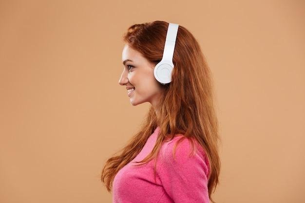 Zijaanzicht dicht omhooggaand portret van een glimlachende roodharigemeisje het luisteren muziek met hoofdtelefoons