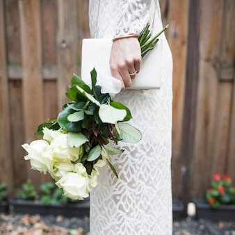 Zijaanzicht die van bruid witte rozen en koppeling houden