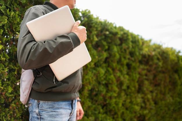 Zijaanzicht die van de mens in openlucht laptop houden