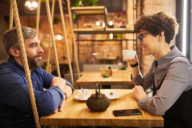Zijaanzicht die van romantisch paar door lijst in gezellig koffiehuis of restaurant zitten, en thee spreken hebben