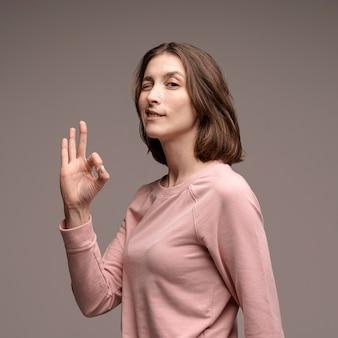 Zijaanzicht die van vrouw en ok teken knipogen maken