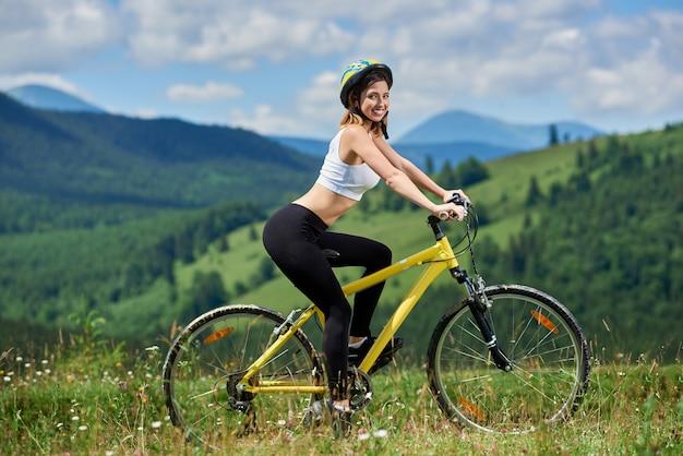 Zijaanzicht die van vrouwelijke ruiter op gele bergfiets op een gras fietsen, die van zonnige dag genieten. bergen, bossen en blauwe lucht buitensportactiviteit