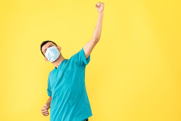 Zijaanzicht dokter in masker een dokter is blij dat hij de patiënt met coronavirus heeft kunnen genezen