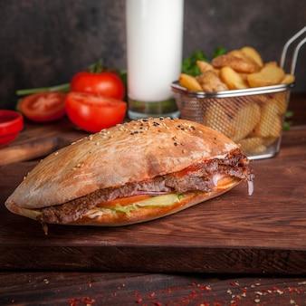 Zijaanzicht doner met tomaat en gebakken aardappelen en ayran in board kookgerei