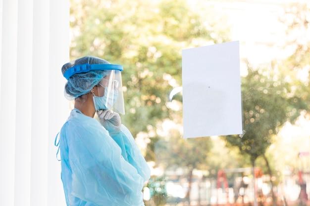 Zijaanzicht doordachte dokter vrouw in beschermende kleding