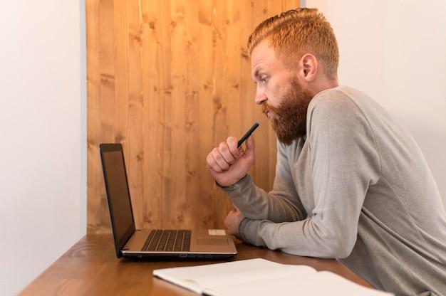 Zijaanzicht doordachte man kijkt naar zijn laptop