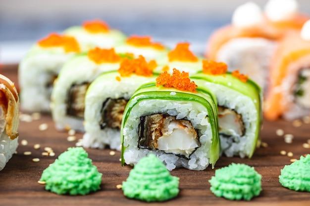 Zijaanzicht dragon roll met komkommer gebakken vis tobiko kaviaar sesamzaadjes en wasabi op een bord