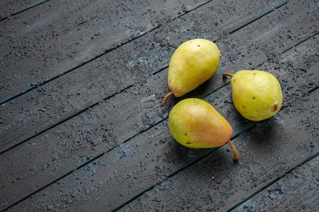 Zijaanzicht drie peren drie groene peren zijn opgemaakt in een cirkel op een grijze achtergrond
