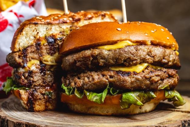 Zijaanzicht dubbele cheeseburger met gegrilde runderpasteitjes, kaas en slablad tussen burgerbroodjes
