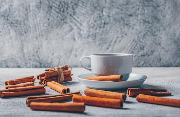 Zijaanzicht een kopje thee met droge kaneel op witte houten en grijze achtergrond. horizontaal