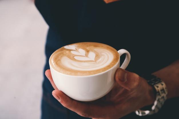Zijaanzicht een man die een kopje cappuccino drinkt