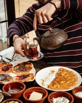 Zijaanzicht een man giet thee ontbijt pannenkoeken en roerei op tafel